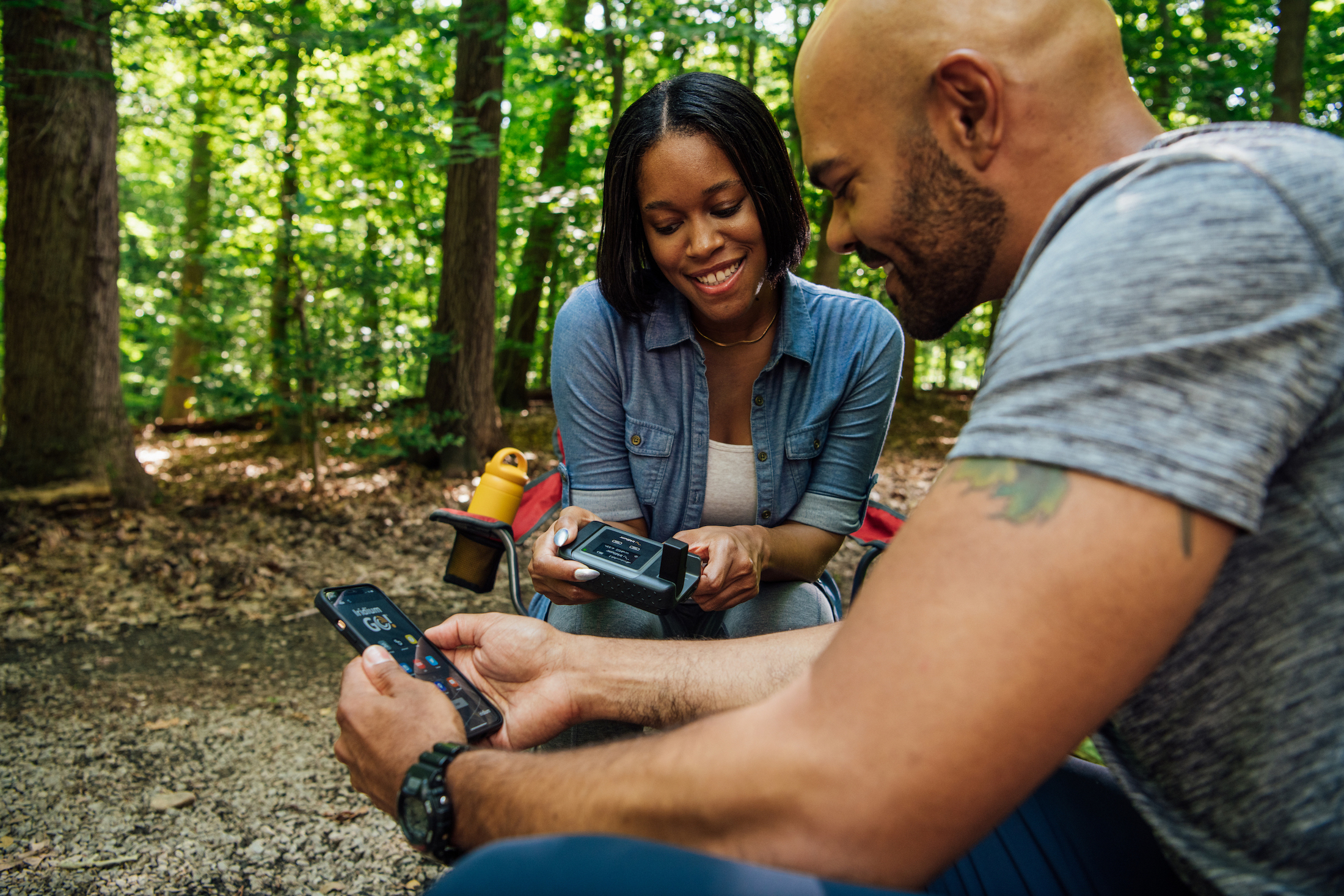 Couple smiling at a campsite in the forest using an Iridium phone