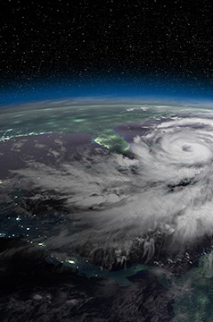 Satellite view of hurrican approaching Florida coastline at night.