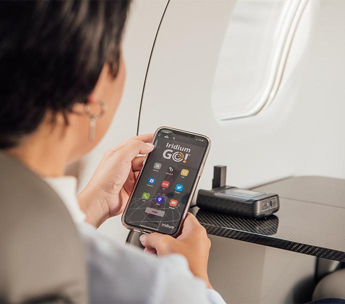 Woman using Iridium GO! on a private plane