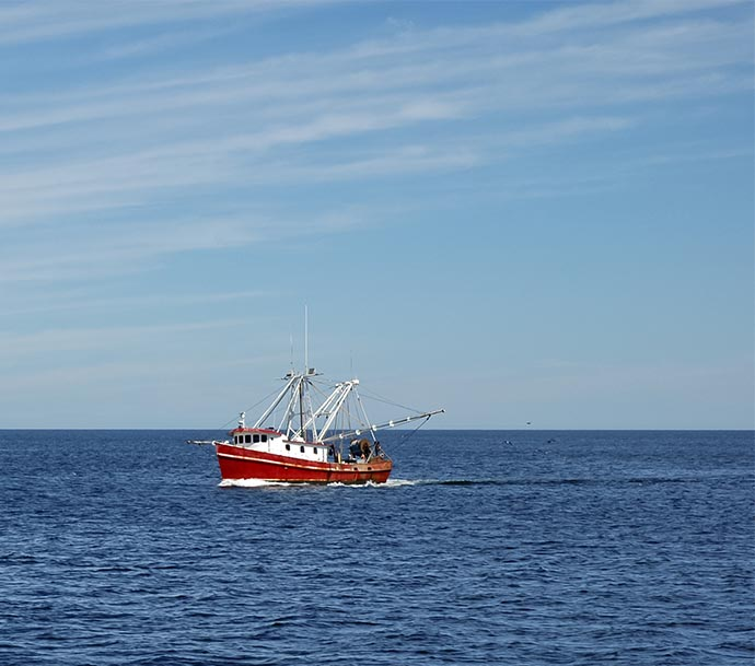 Image of a small fishing vessel out at sea, isolated